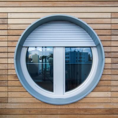 Kulaté okno s roletou v dřevěném fasádním obkladu